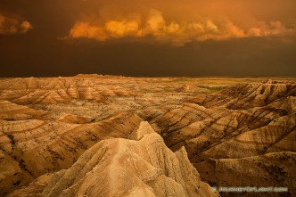 Facing east, the sky was nearly pitch black shrouded by the fierce storm that had just passed through. As the sun dipped below the horizon the last rays hit the trailing storm clouds and the ambient warm light lit up the valley across the Badlands in South Dakota.