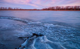 In early winter, sunrise hits the landscape illuminating the forming ice on the lake at DeSoto National Wildlife Refuge.
