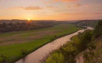 The Niobrara is one of the most popular rivers for canoeing and tubing in the United States. On a beautiful spring sunrise, the river lazily meanders into the east as the sun rises in the distance.