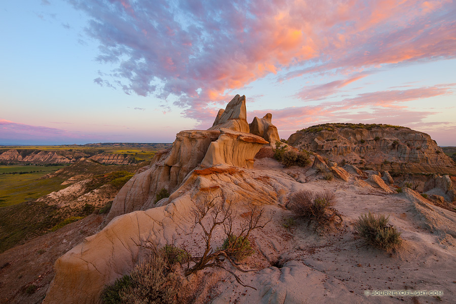The warm glow of the rising sun illuminates badlands in western North Dakota in Theodore Roosevelt National Park.