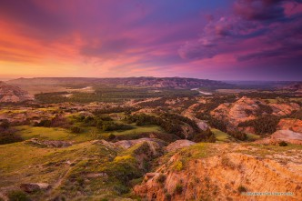 Above a bend in the Little Missouri River in the North Unit of Theodore Roosevelt National Park, clouds glow purple and orange as the sun just begins to rise above the horizon.