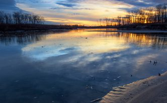 Pawprints from a racoon are illuminated on the shore as the sun rises over the Missouri River at Ponca State Park in northeastern Nebraska.