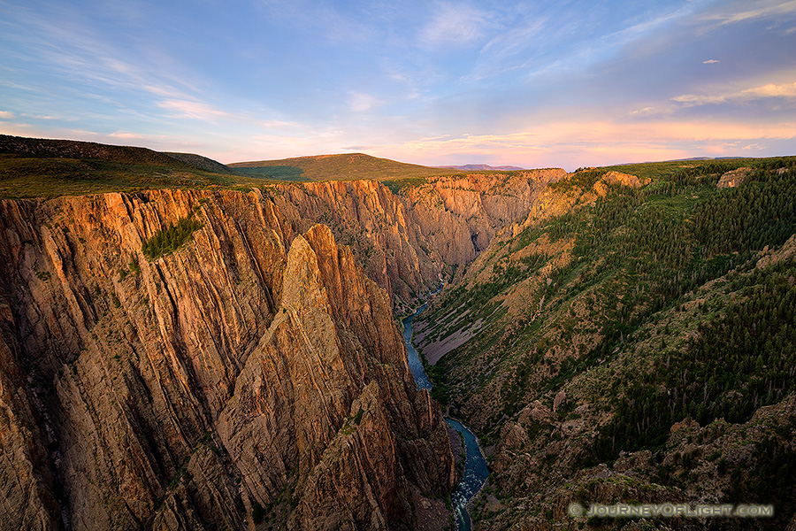 As the sun sets in the west in Black Canyon of the Gunnison National Park, the last glow of the day skims the canyon walls to the east.