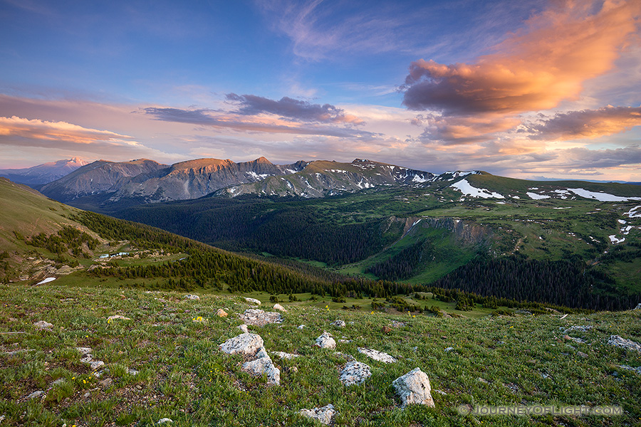 Clouds gather above the tops of the mountains in Rocky Mountain National Park as the last warm glow of sunset grazes the peaks.