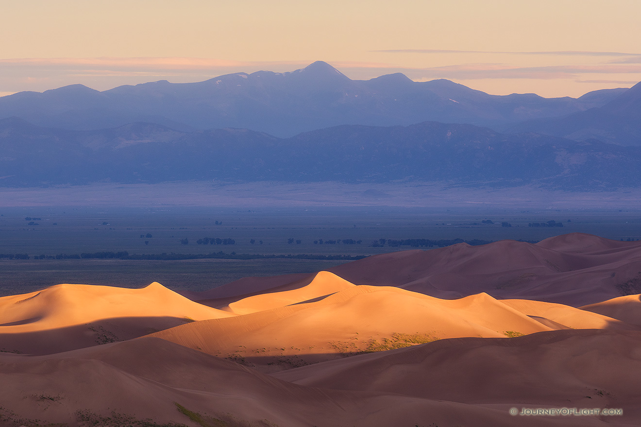 Light graces the tops of the Sand Dunes in the distance as the sun peaks over the Sangre De Cristo range.