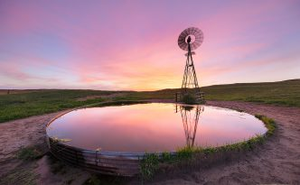 The western sky glows with beautiful pinks, purples, and oranges behind a windmill reflected in the full tank.