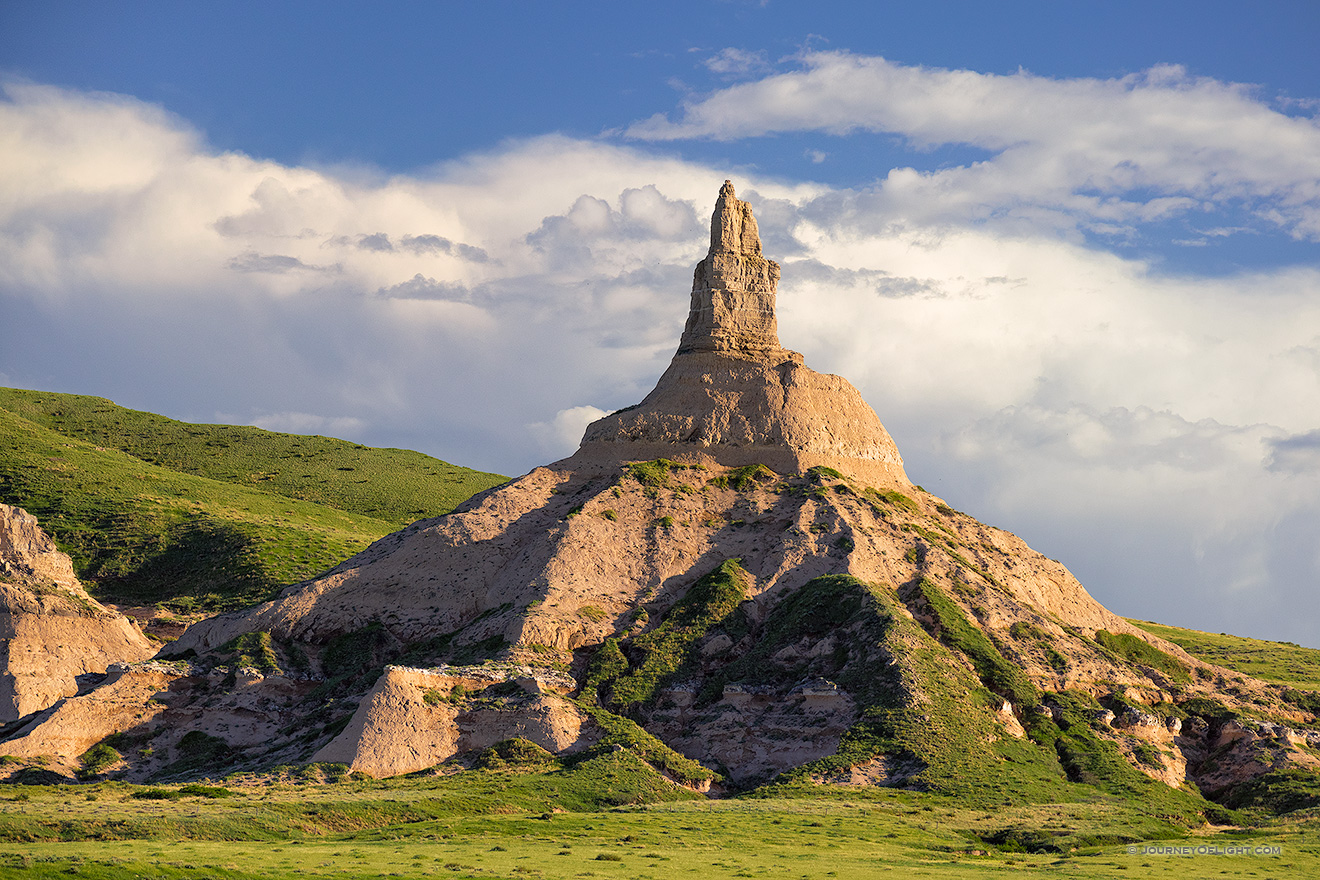 Clouds gather behind Chimney Rock as the glow of the late afternoon sun illuminates its western side.