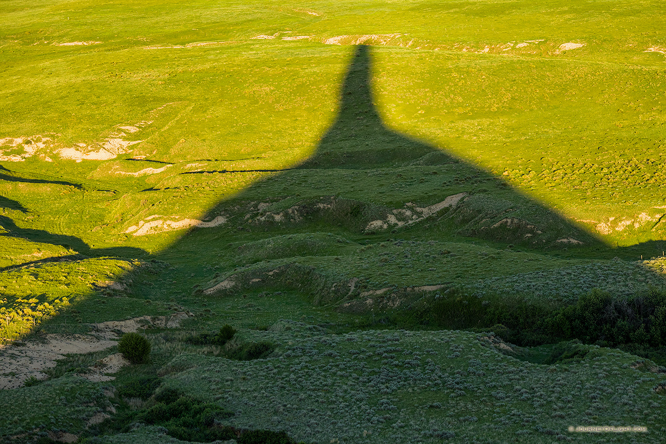 Chimney Rock's shadows stretches out across the plains as the sun dips low in the western sky.