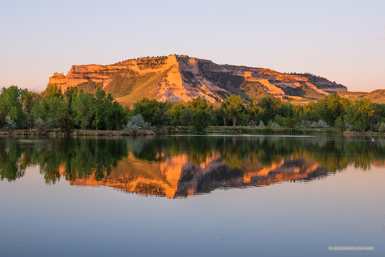 Glowing in the light of the recently risen sun, Scotts Bluff National Monument in western Nebraska is reflected in a small nearby lake.