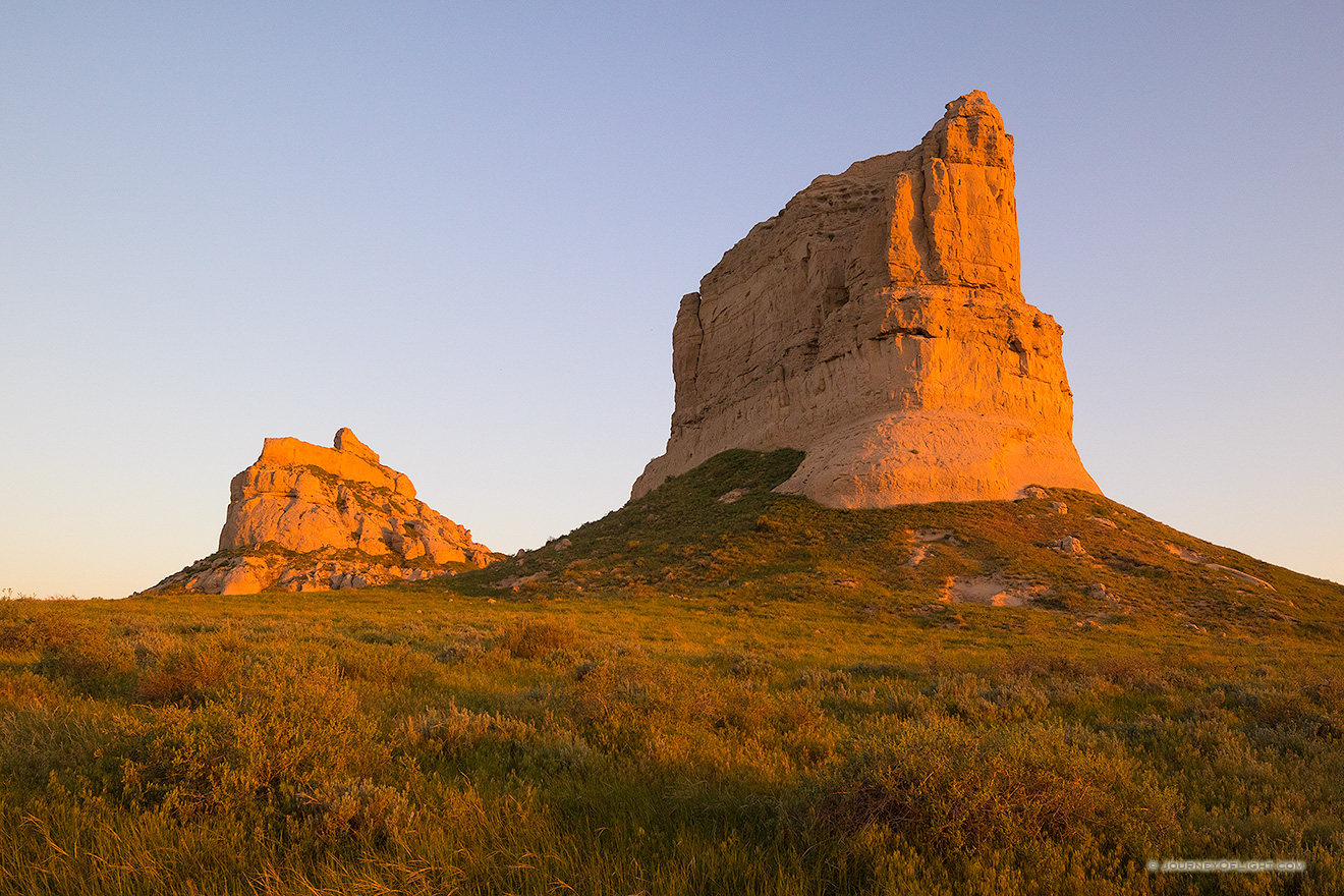 Jailhouse and Courthouse Rock both glow red with the first light at sunrise.