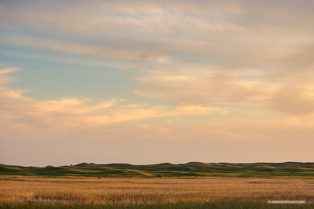 The last light of sunset skims across the Nebraska Sandhills and casts a warm glow on the clouds above.