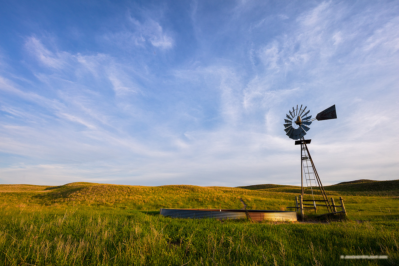 Late afternoon sun illuminates an abandoned windmill deep in the Sandhills of Nebraska.