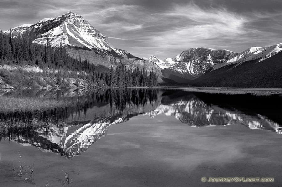 Only a small ripples disturbs the reflection of the mountains in the distance canada