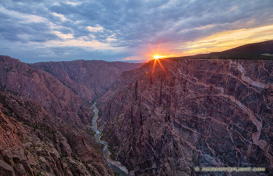 The last bit of sun hangs just above the canyon wall at Black Canyon of the Gunnison National Park on a cool summer evening. - Colorado Photography