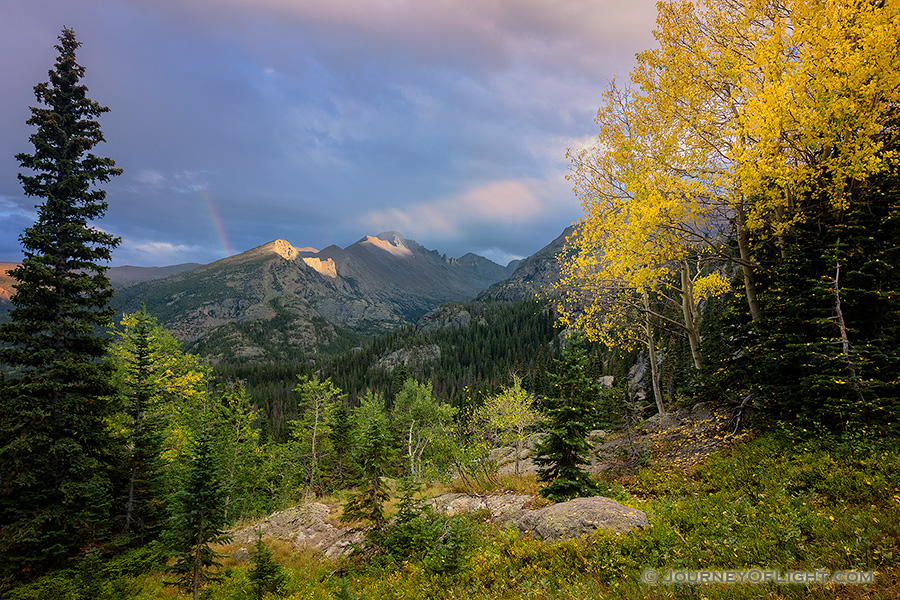 On a cool autumn evening sun strikes the peak of Long's Peak in Rocky Mountain National Park.  A faint rainbow briefly appeared as the storm moved over the mountain. - Colorado Photography