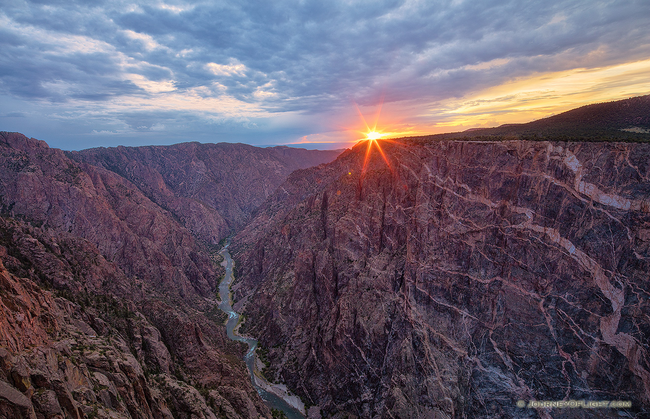 The last bit of sun hangs just above the canyon wall at Black Canyon of the Gunnison National Park on a cool summer evening. - Colorado Picture