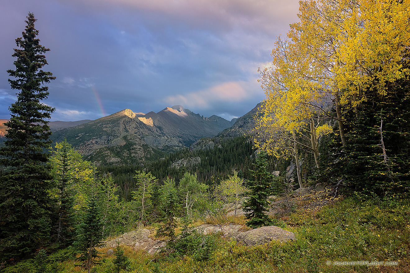 A photograph of Longs Peak in Rocky Mountain National Park with a Rainbow and Yellow Aspen Trees.