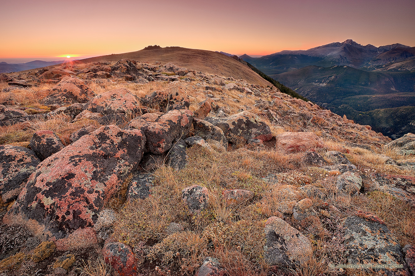 On this day, as many days through time, the exposed rocks on the tundra area of Rocky Mountain National Park bear witness to the rising sun and its illumination of Longs Peak. - Colorado Picture