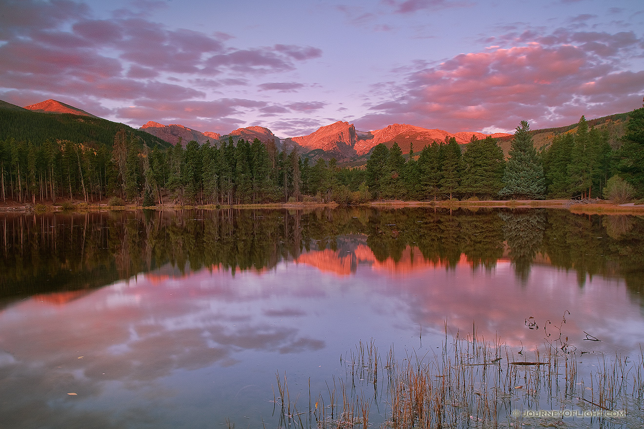 During a cool October sunrise, bright with alpenglow, the peaks of the continental divide, Powell Peak, Taylor Peak, Otis Peak, Hallett Peak, and Flattop Mountain are reflected in the calm waters of Sprague lake while underlit clouds hover overhead. - Rocky Mountain NP Picture