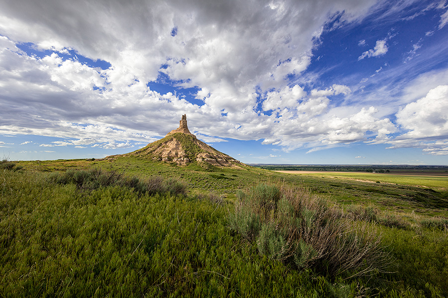 On a cool spring day, under a beautiful blue sky filled with puffy white clouds, Chimney Rock glows in the warm light of the afternoon sun. - Nebraska Photography