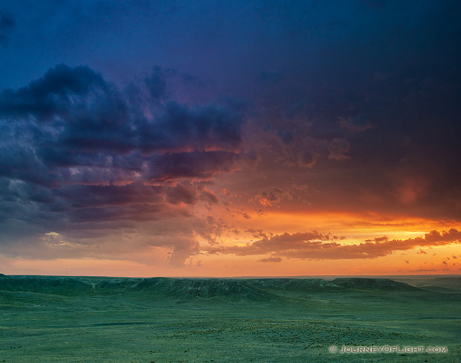 The verdant prairie grass appears as a green carpet in the valleys of Agate Fossil Beds National Monument in western Nebraska as the last bit of sunlight radiates from beneath the dark storm clouds.  From a high perch, I watched this storm as it moved past, the clouds changing and morphing. - Nebraska Photography