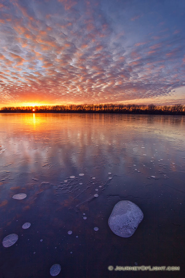 The warm setting sun shines brightly across the frozen lake on a chilly January evening before dipping below the horizon. - DeSoto Photography