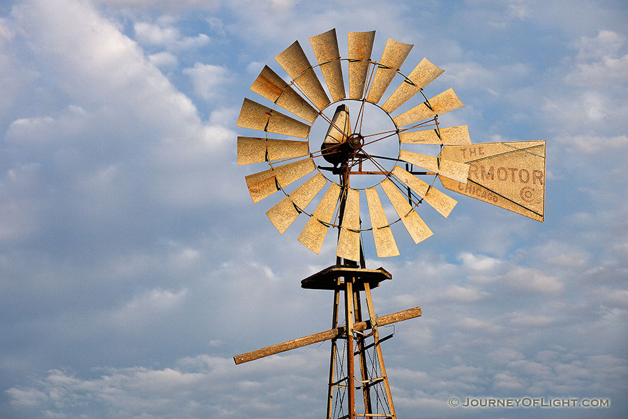 In rural Dixon County in Northeastern Nebraska a still windmill reflects the golden light of the rising sun against a cloudy sky. - Nebraska Photography