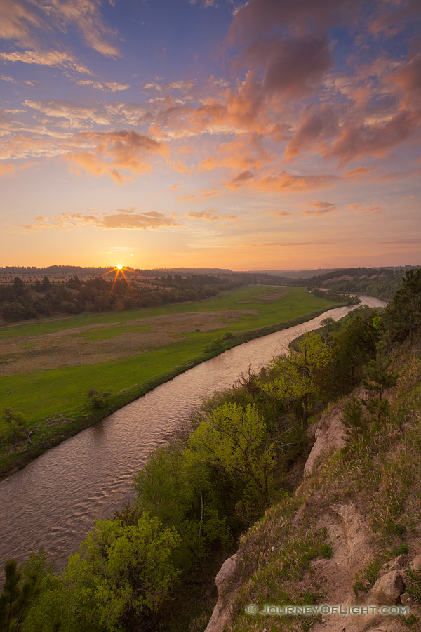 The Niobrara is one of the most popular rivers for canoeing and tubing in the United States.  On a beautiful spring sunrise, the river lazily meanders into the east as the sun rises in the distance. - Valentine Photography