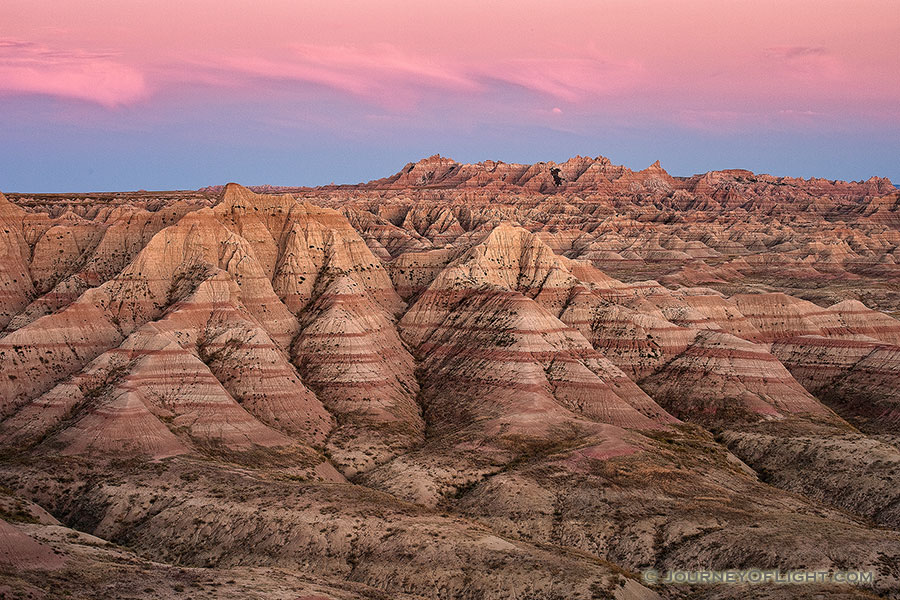 Pink clouds float above Badlands National Park while the rocky terrain below is bathed in the warm light just after sunset. - South Dakota Photography