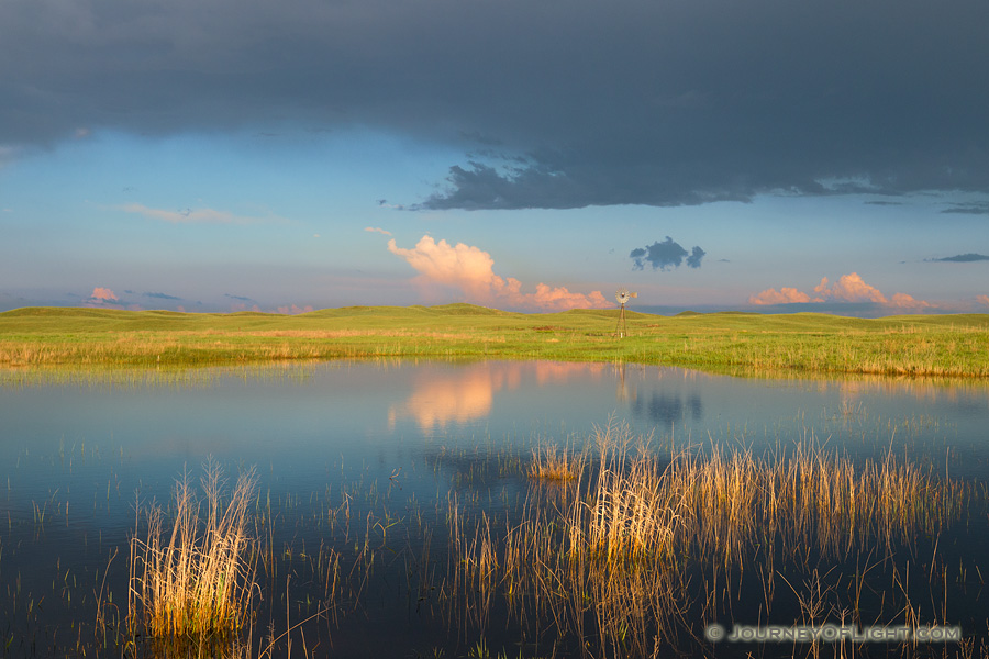 A windmill and storm clouds are reflected in a small lake in the Sandhills of Nebraska. - Nebraska Photography