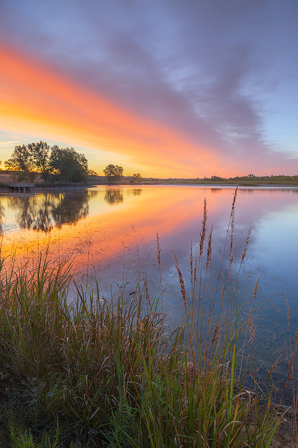 A landscape photograph of a sunrise reflected in a lake at Mahoney State Park, Nebraska. - Nebraska Photography