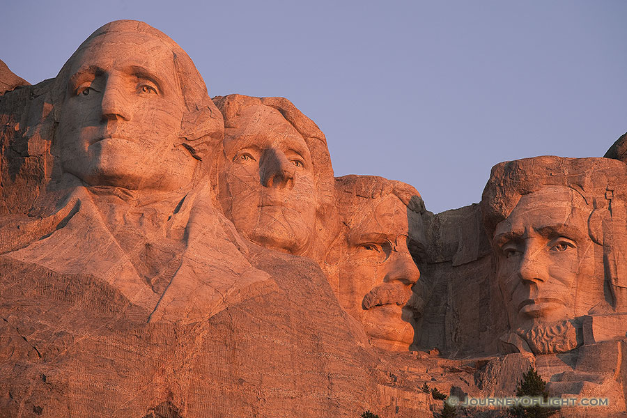 The warm sunrise light illuminates the faces with a reddish hue. - Mt. Rushmore NM Photography