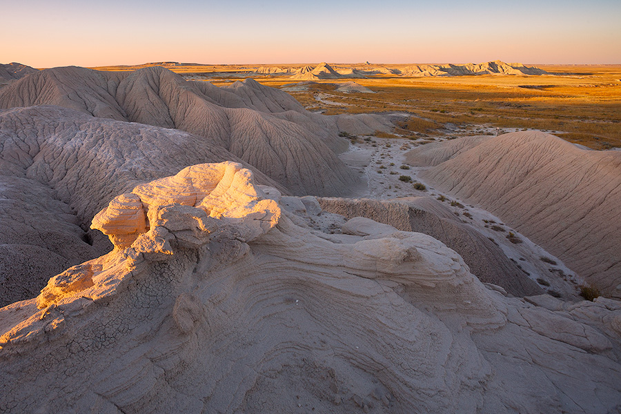 As the sun sets warm sunlight bathes parts of Toadstool Geologic Park in warm hues. - Toadstool Geologic Park Photography