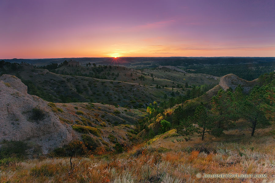 On an early fall morning, the rising sun shines brightly across Chadron State Park, in western Nebraska. - Nebraska Photography