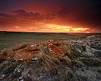 Evening descended and dark clouds moved slowly across the sky to the north on a cool, spring evening at Agate Fossil Beds National Monument in far western Nebraska.  As the sun set in the west, it's orange glow illuminated the scene with fiery oranges and reds, briefly before being lost below the horizon. - Nebraska Landscape Photograph