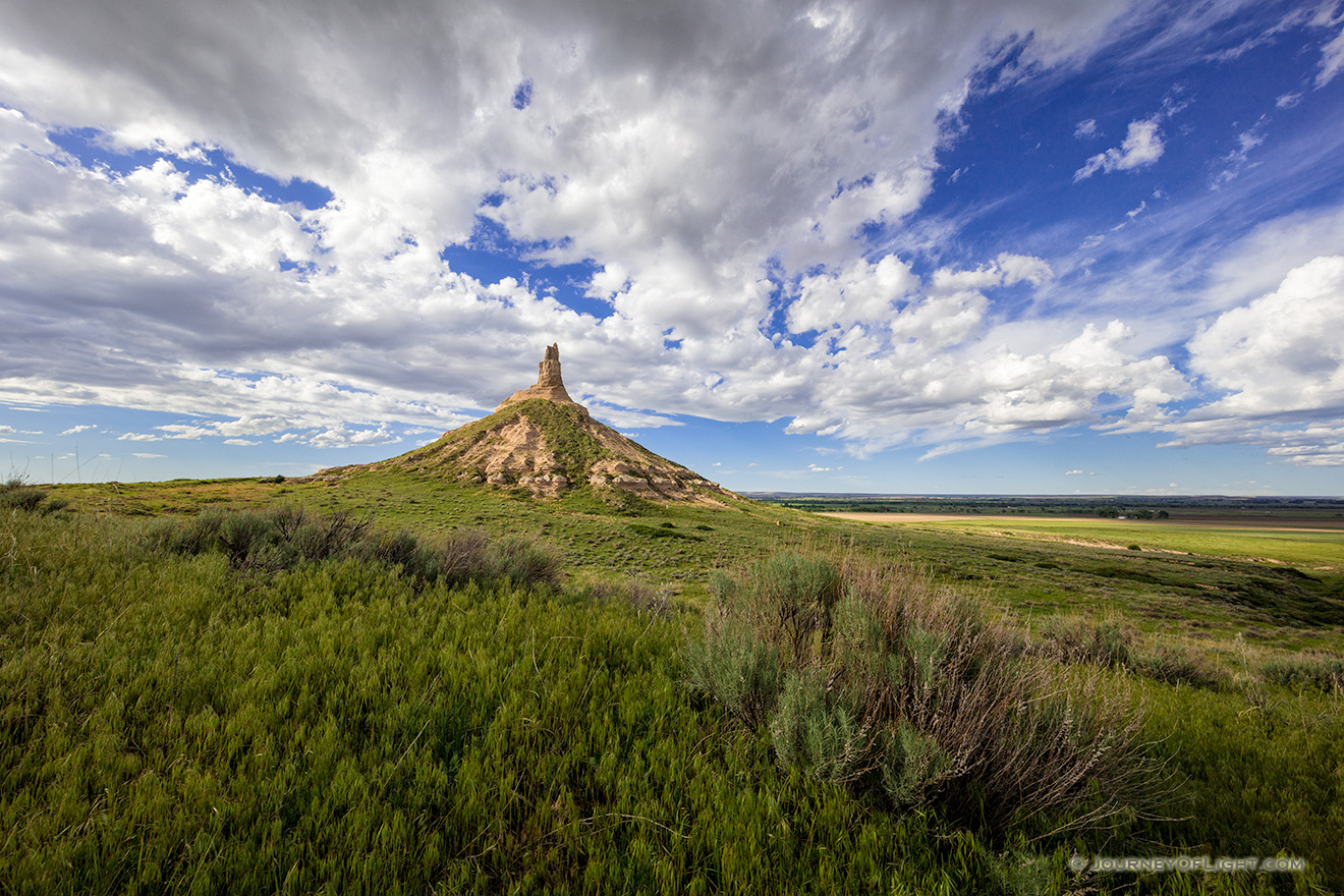 On a cool spring day, under a beautiful blue sky filled with puffy white clouds, Chimney Rock glows in the warm light of the afternoon sun. - Nebraska Picture