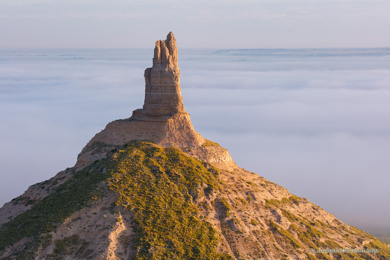 A scenic landscape photograph of Chimney Rock National Historic Site in fog. - Nebraska Picture
