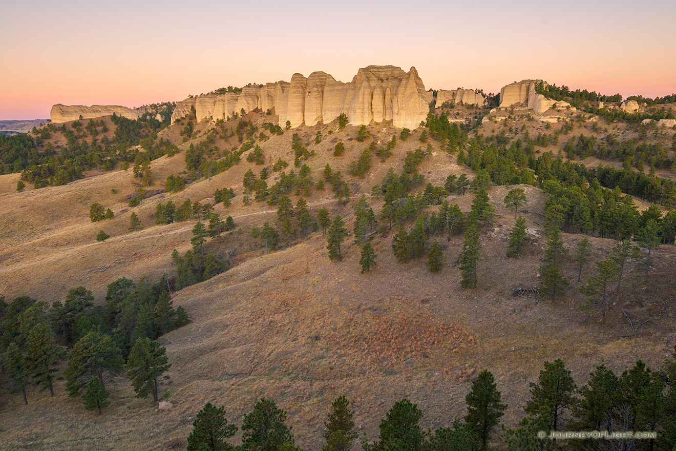 A scenic landscape photograph of the sunrise on the Red Cloud Buttes at Ft. Robinson in Northwestern Nebraska. - Nebraska Picture