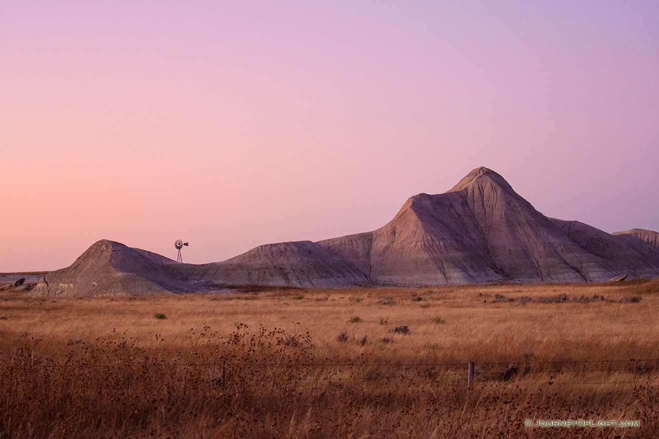 Scenic landscape photograph of a windmill and badlands during dusk in western Nebraska. - Nebraska Picture