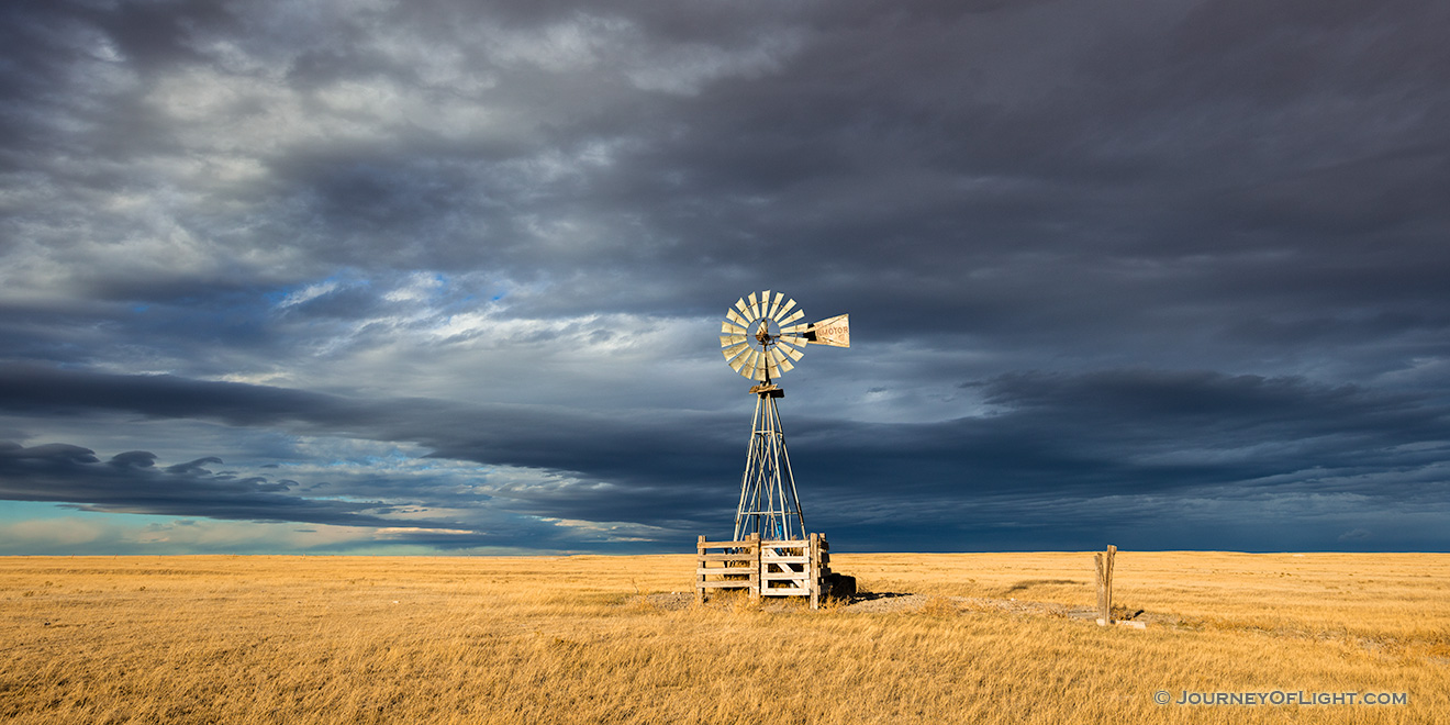 Scenic landscape panoramic photograph of a windmill and a storm at Oglala National Grasslands. - Nebraska Picture
