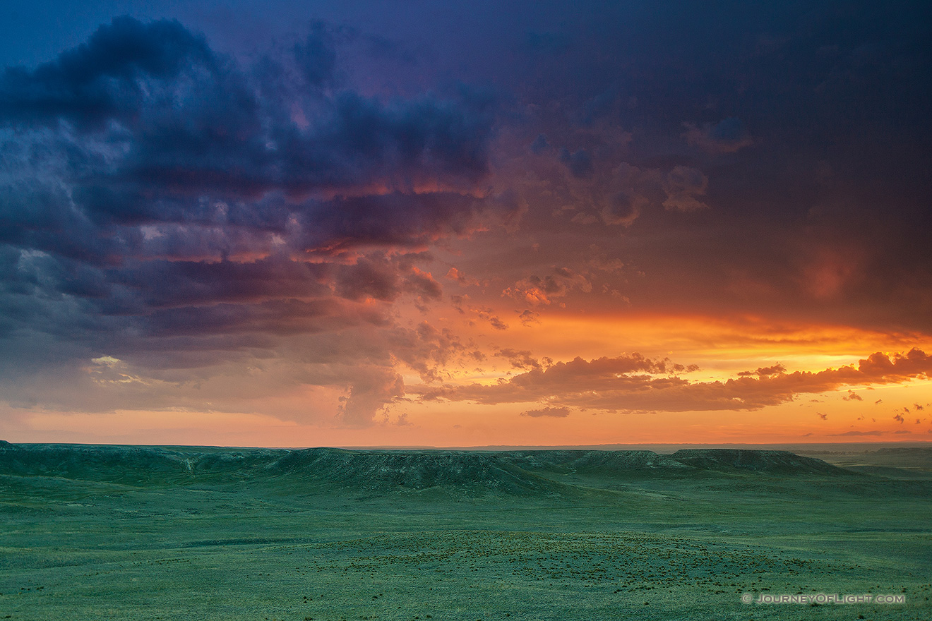 The verdant prairie grass appears as a green carpet in the valleys of Agate Fossil Beds National Monument in western Nebraska as the last bit of sunlight radiates from beneath the dark storm clouds.  From a high perch, I watched this storm as it moved past, the clouds changing and morphing. - Nebraska Picture