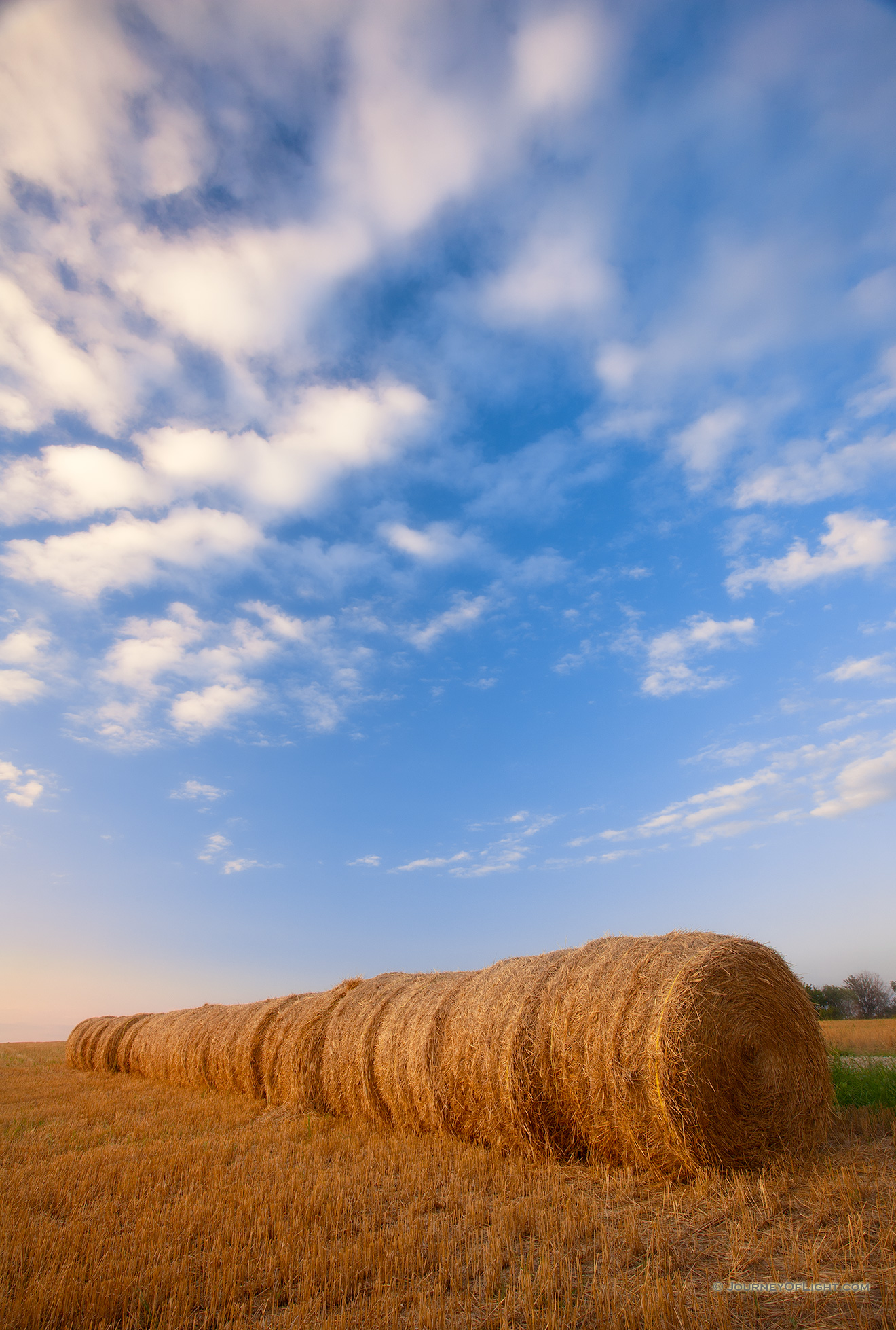 Puffy clouds form in the late evening above a row of hay bales in eastern Nebraska. - Nebraska Picture
