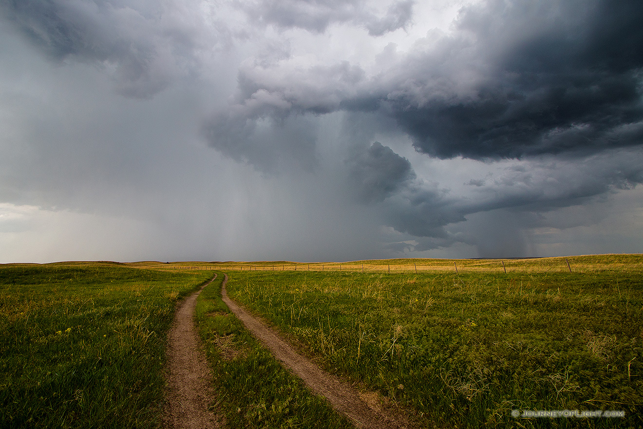 An ominous storm hovers over a two track in McKelvie National Forest.  The clouds slowly roll through dropping rain over the sandhills while lightning lights up the sky and the sound of thunder fills the air. - Sandhills Picture