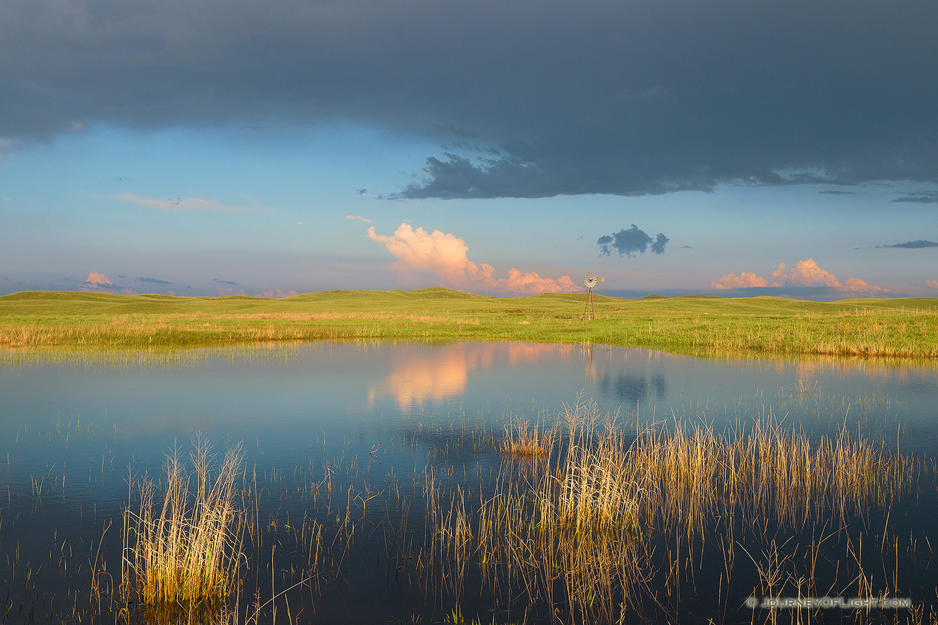A windmill and storm clouds are reflected in a small lake in the Sandhills of Nebraska. - Nebraska Picture