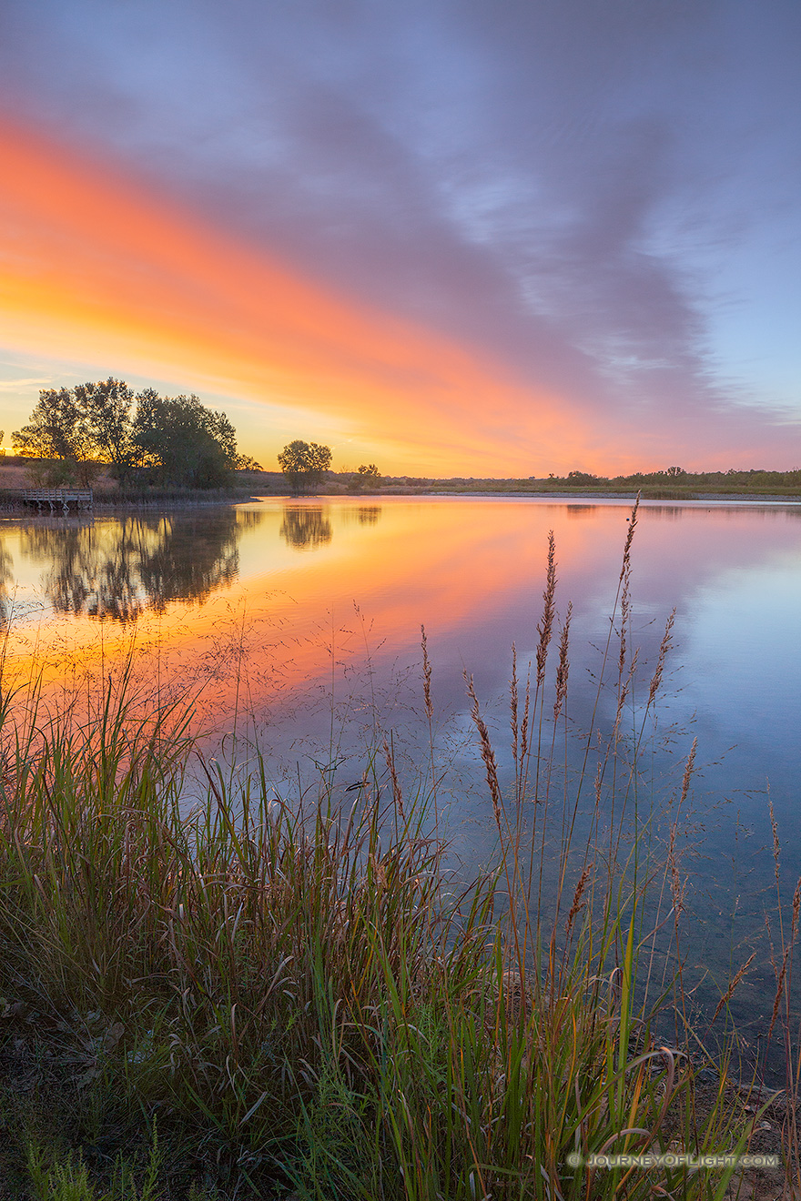 A landscape photograph of a sunrise reflected in a lake at Mahoney State Park, Nebraska. - Nebraska Picture