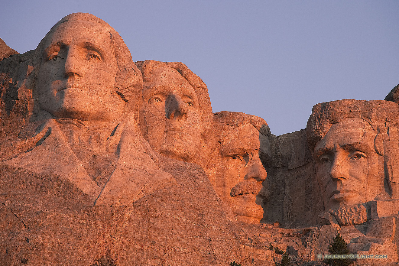 The warm sunrise light illuminates the faces with a reddish hue. - Mt. Rushmore NM Picture