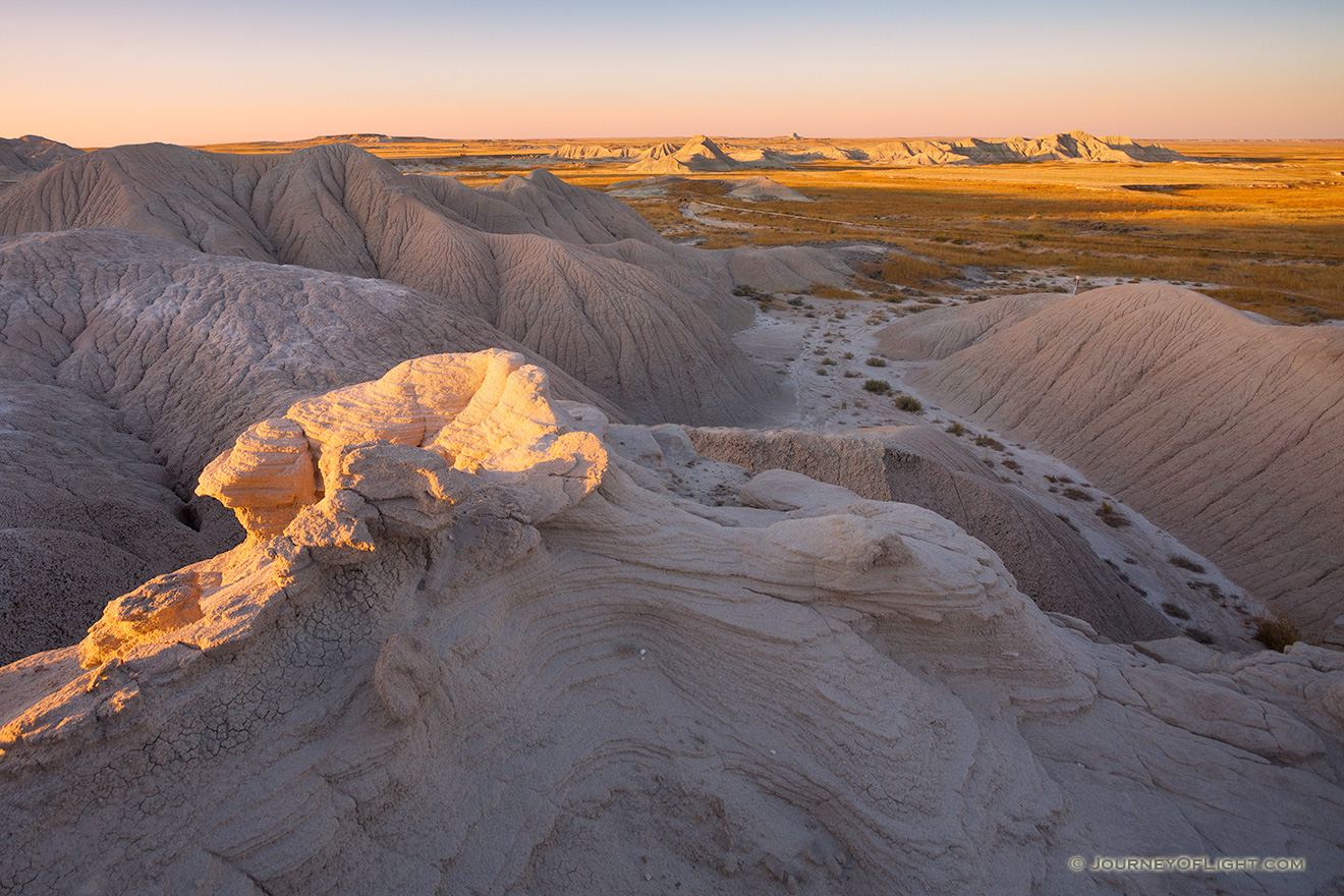 As the sun sets warm sunlight bathes parts of Toadstool Geologic Park in warm hues. - Toadstool Geologic Park Picture