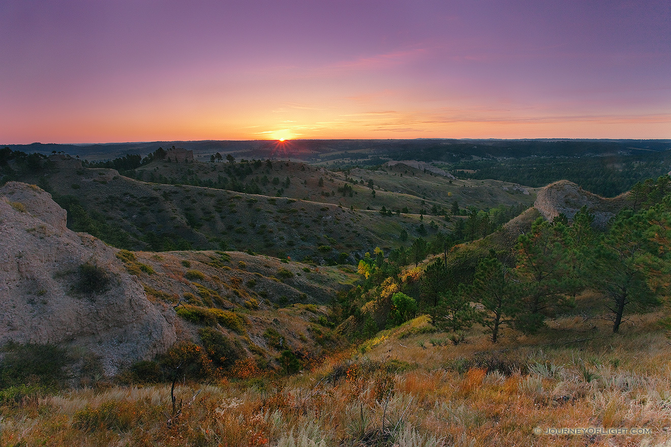 On an early fall morning, the rising sun shines brightly across Chadron State Park, in western Nebraska. - Nebraska Picture